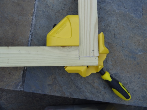 Making a canvas stretcher frame, aligning corner lap joint with frame clamps. Photo credit Kelise Franclemont.
