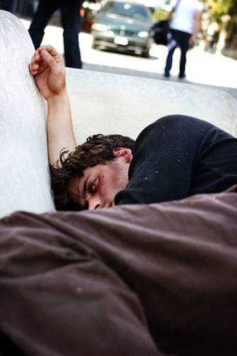 actor Francois Arnaud depicted sleeping rough, in 'What Makes Us Care?' at The Crypts gallery, St Martins-in-the-Fields, London. Photography by Kathryn Prescott.