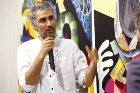 Iraqi artist Athier talks about his work in 'Man of War' exhibition at Edge of Arabia, London. Image courtesy Edge of Arabia.