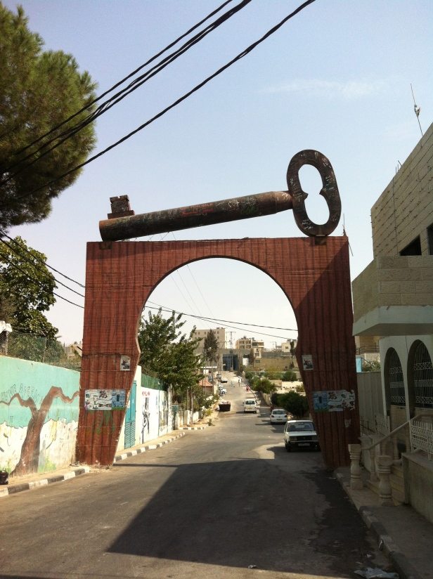 One of the many key sculptures, symbolising the refugees right to return someday to their homes. This one is adjacent to Aida refugee camp (you can see the wall at left of photo). Aida camp is situated near Bethlehem. Photo credit Tom Butler.