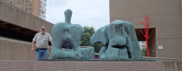 Al P. at the exterior of Everson Museum of Art. Sculpture by Henry Moore (foreground), 'Two Piece Reclining Figure: No.3', 1961, bronze. Photo credit Kelise Franclemont.