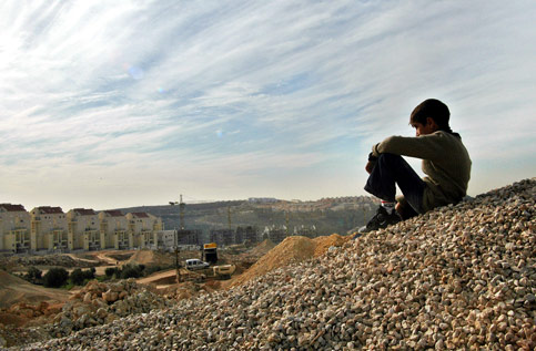 A Palestinian boy from Bilin outside Ramallah sits over an Israeli settlement being constructed next to the village, December 2005. Image courtesy www.electronicintifada.net. Photo credit: Charlotte de Bellabre/MaanImages.