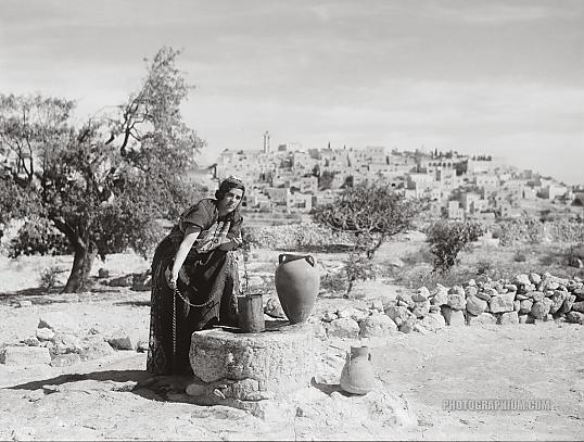 Bethlehem from south with woman figure, Sofie at the well, clad in richly embroidered costume and drawing water. Bethlehem, Palestine, 1938. Photographer unknown. Image courtesy http://www.photographium.com/