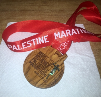 A Palestine Marathon finisher's medal made of olive wood and mother-of-pearl. Photo credit Kelise Franclemont.
