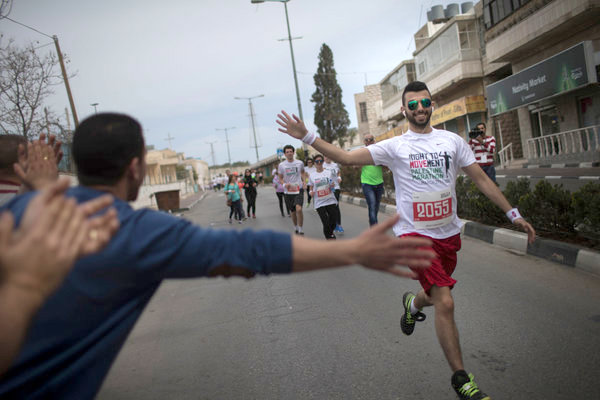 Runner receiving encouragement from a spectator in the Palestine Marathon, 2015, Bethlehem, Palestine (Occupied Territories). Photo courtesy Uriel Sinai for New York Times
