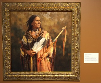 Krystin Melaine, 'War and peace', 2008, oil on canvas, at Booth Western Art Museum, Cartersville, GA. Photo credit Kelise Franclemont. The card reads: 'A native of Australia, Melaine knew she wanted to be an artist. Her interest in Western American subjects emerged from her numerous trips to the United States. Although this Plains Indian subject wears the shirt of a warrior, he holds a peace pipe.'
