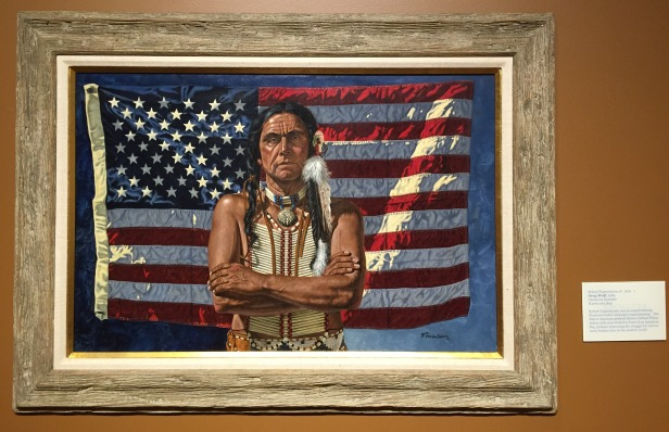Robert Tannenbaum, 'Grey Wolf', 1984, casein on masonite, at Booth Western Art Museum, Cartersville, GA. Photo credit Kelise Franclemont. The card reads: Robert Tannenbaum was an award-winning illustrator before turning to easel painting. This Native American portrait shows a defiant Plains Indian with arms folding in front of an American flag, perhaps expressing the struggle for success many Indians face in the modern world.'