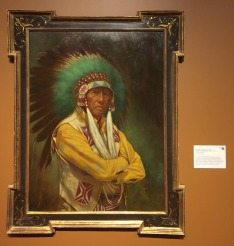 """Michael C Poulsen, 'Chief Joe Medicine Crow', 1998, oil on masonite, at Booth Western Art Museum, Cartersville, GA. Photo credit Kelise Franclemont. The card reads: 'This portrait exhibits the influence of classic European art which Poulsen brought back from studies abroad...the sitter once auditioned for a role in a Western movie but was rejected because, """"he didn't look Indian enough"""".'"""