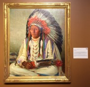 Kathryn Woodman Leighton, 'The referee', 1926, oil on canvas, at Booth Western Art Museum, Cartersville, GA. Photo credit Kelise Franclemont. The card reads: 'Charles M Russell introduced Leighton to important Blackfeet Indian leaders in 1925, during her family's vacation to Glacier National Park. She returned next summer to paint a series of their portraits. The Great Northern Railroad bought twenty of these and sent them on a cross-country tour. The sitter holds and eagle-tail fan, decorated with peacock feathers, showing how current fads sometimes modified traditional Indian apparel. Fashion-conscious Americans of the 1920s often used peacock feathers for decoration.'