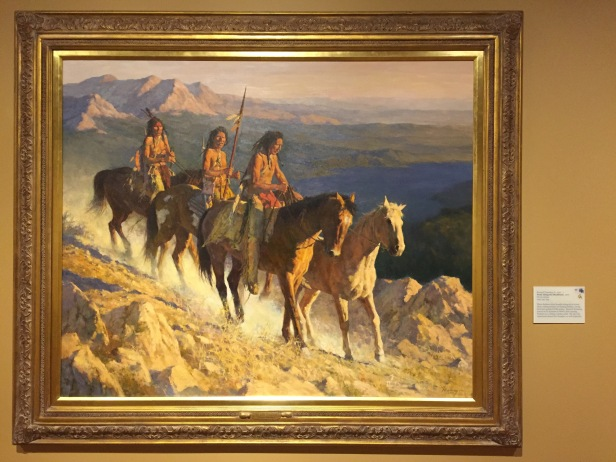 Howard Terpning, 'Trail along the backbone', 2001, oil on canvas at Booth Western Art Museum, Cartersville, GA. Photo credit Kelise Franclemont. The card reads: 'Plains Indians often brought along extra horses when raiding enemies or hunting buffalo, saving their best ponies for the action. Terpning served in the Marines in WWII, later touring Vietnam as a civilian combat artist. He says this experience shaped his thoughts on native peoples.'