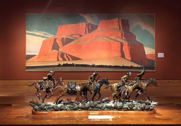 (foreground) Truman Bolinger, 'Rendezvous, Rendezvous', 1973, bronze, and (background) L. Maynard Dixon, 'Red Butte with Mountain Men', 1935, oil on canvas, at Booth Western Art Museum, Cartersville, GA. Photo credit Kelise Franclemont. The card reads: 'In this mural Dixon's simplified shapes, strong desert colors, and vast landscape forms make Kit Carson and his band of frontiersman appear insignificant... this is one of a pair of murals with a similar theme installed behind one of the two cocktail bars in the Kit Carson Steak Restaurant in San Francisco (now demolished).'