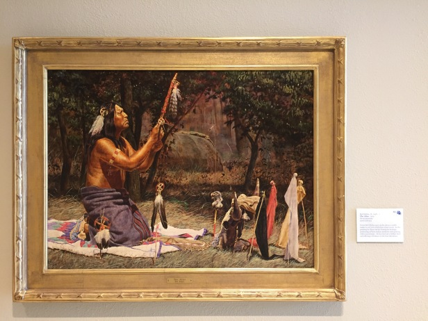 Bob Moline, 'The Altar', 1974, oil on masonite, at Booth Western Art Museum, Cartersville, GA. Photo credit Kelise Franclemont. The card reads: 'Texan Bob Moline gave up his full-time job as a saddle-maker in 1973 for a full-time career in art. In this painting, he draws on his Comanche heritage, portraying a Plains Indian medicine man praying with a sacred pipe. He has laid out a buffalo skull and offerings of tobacco to the four directions.'