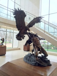 Vic Payne, 'Eagle Catcher', 1996, bronze at Booth Western Art Museum, Cartersville, GA. Photo credit Kelise Franclemont. The card reads: 'Legends tell of capturing the Golden Eagle by the Plains Indian, who believed their feathers were infused with wisdom. These coveted feathers, when displayed in a war bonnet, symbolised the capture of the essence of the Great Spirit. A brave obtained an eagle feather to represent each heroic strike he inflicted on an enemy combatant. Only after a warrior earned 29 or 30 feathers, did he earn the right to build a bonnet to display them all and become an 'Eagle Catcher'.'