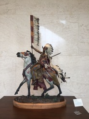 David Manuel, 'Victory coup', 1994, bronze and polychrome, at Booth Western Art Museum, Cartersville, GA. Photo credit Kelise Franclemont. The card reads: 'David Manuel grew up in Walla Walla, Washington, but now resides in nearby Joseph, Oregon, where he operates a museum, art school, sculpture studio, and a bed and breakfast. Among the many awards and commissions Manuel has received was his recognition as the official sculptor for the 150th Anniversary Celebration of the Oregon Trail.'