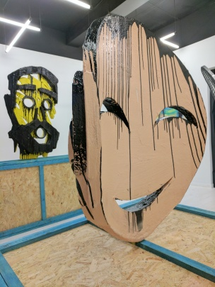 Adam Zoltowski, (background) 'Blackbeard' and (foreground) 'Portrait of Monika', 2016, wood, polyurethane, Jesmonite, fibreglass, spray paint, bitument, steel, in 'Foreign Bodies', 242 Cambridge Heath Road, London. Image courtesy the artist.
