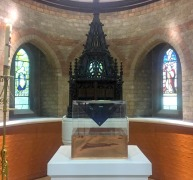 Acrylic cube with a copper base, 36 centimetres square, placed in front of the baptismal font in the nave of the church. The acrylic box contains a hologram of a drop of water falling upwards.