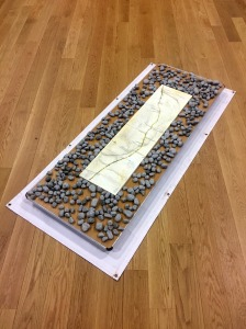 A large platform 1 by 3 meters rectangle, wooden, on top of which is a row of four tiles that make a map of a river in South Dakota. The tiles are surrounded by grey river stones.